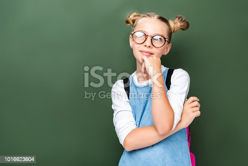 1016623732istockphoto pensive schoolchild in glasses looking up near blackboard 1016623604