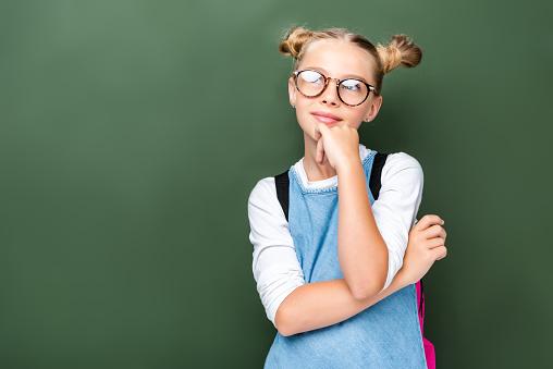 1016623732 istock photo pensive schoolchild in glasses looking up near blackboard 1016623604