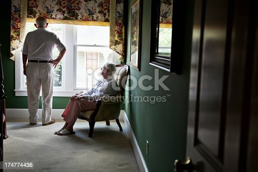 istock Pensive senior couple looking out window 174774436