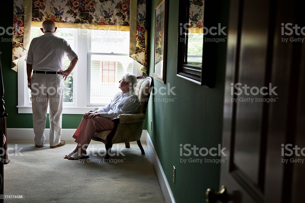 Pensive senior couple looking out window stock photo