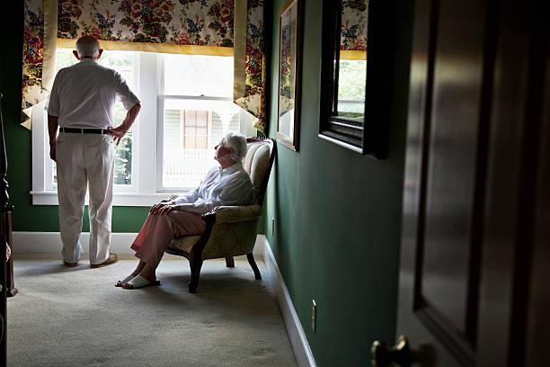 pensativo casal idoso, olhando para fora da janela - old men window imagens e fotografias de stock