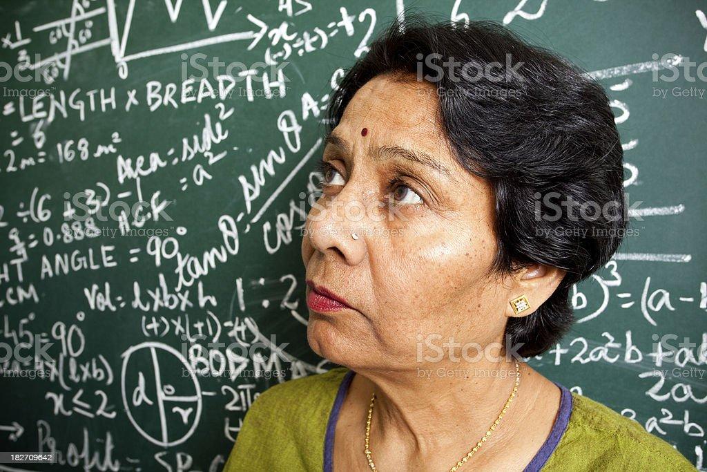 Pensive Senior Indian Mathematics Teacher in a Classroom royalty-free stock photo