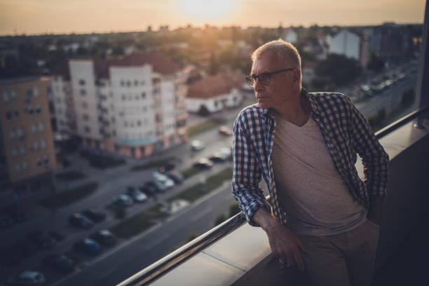 nachdenklich senior woman genießen den blick von seinem penthouse balkon bei sonnenuntergang. - seniorenwohnungen stock-fotos und bilder