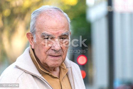 Pensive hispanic senior man looking at the camera