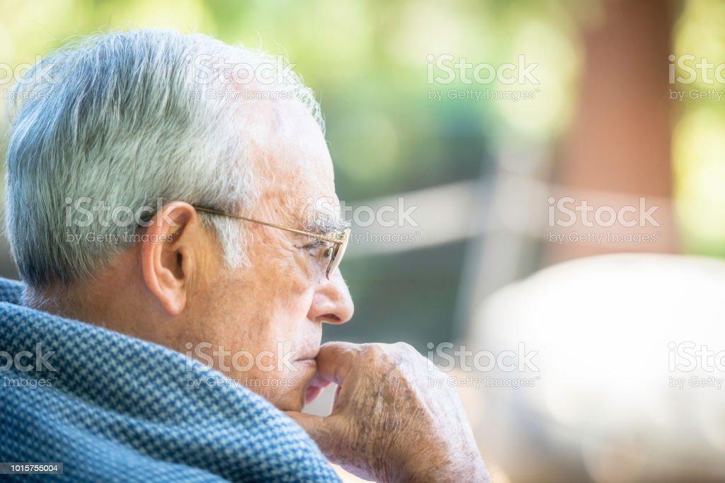 Pensive senior man looking away stock photo