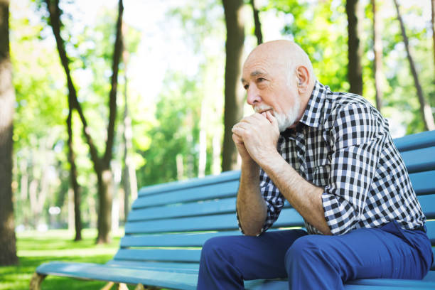 Pensive senior man outdoors Thoughtful senior man outdoors. Elderly man in casual sitting on the bench in sunny park, copy space introspection stock pictures, royalty-free photos & images