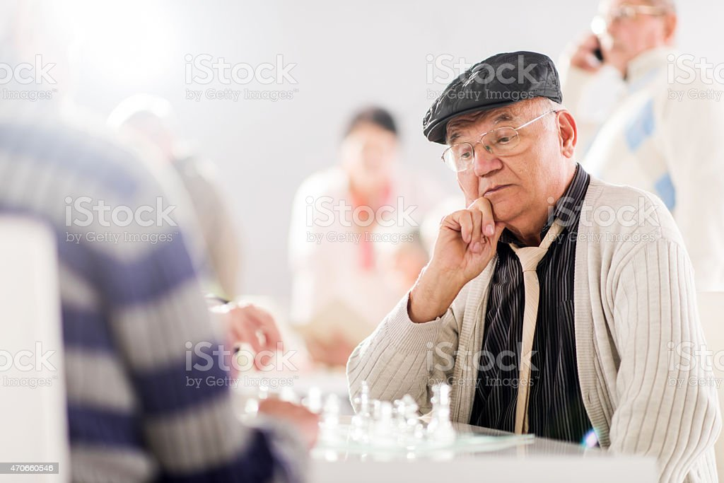 Pensive senior man playing chess with his friends. stock photo