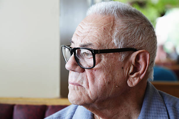 Pensive Senior Man Sitting Alone and Looking Out Window stock photo