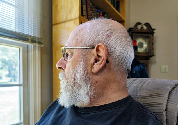 Pensive Senior Man Staring Out Home Living Room Window stock photo