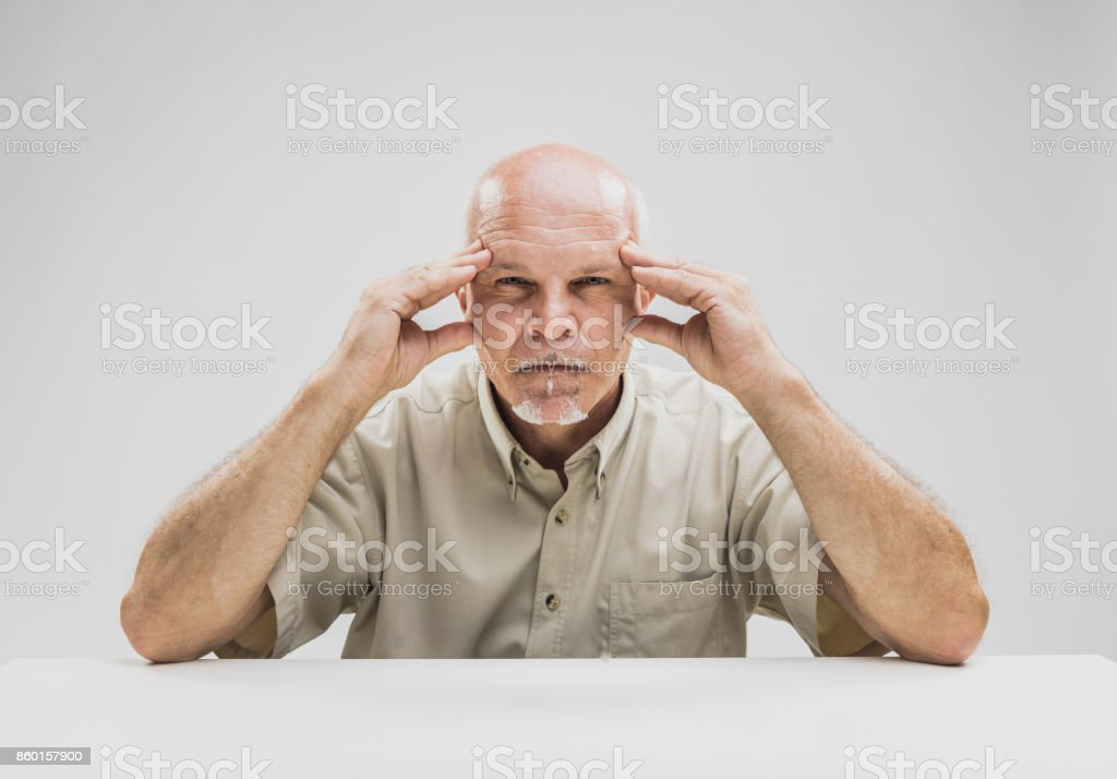 Pensive senior man with a focused expression stock photo