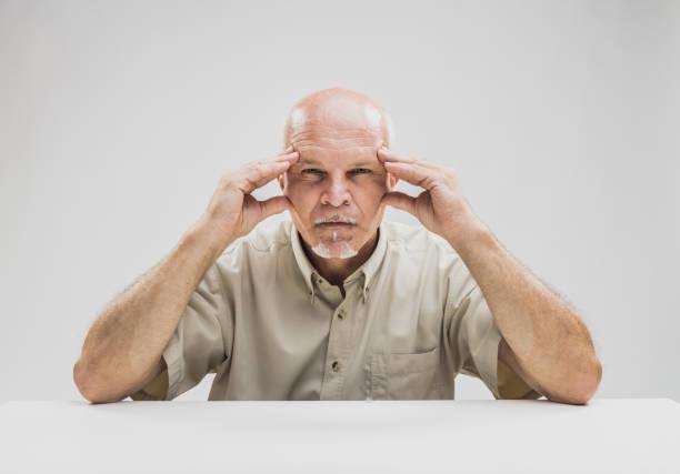 nachdenklich senior mann mit einem konzentrierten ausdruck - gedanken lesen stock-fotos und bilder
