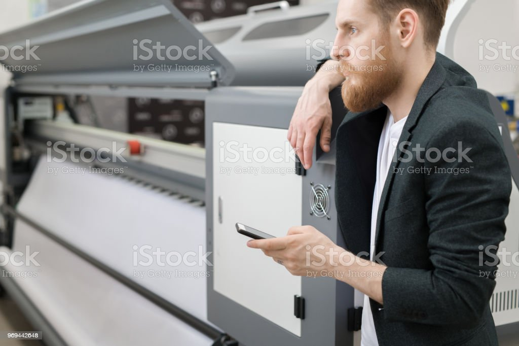 Pensive serious hipster handsome young male engineer in black jacket leaning on large scale format printer and thinking about sms while working in printing house stock photo