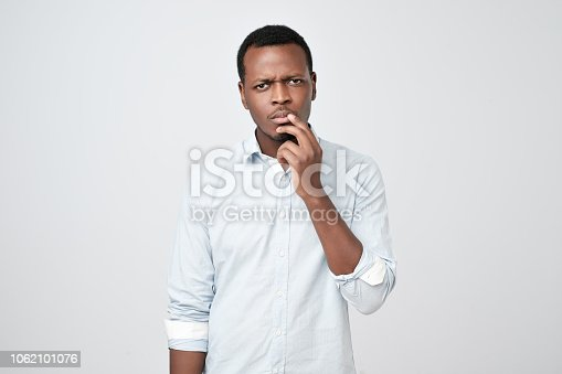 Studio shot of pensive serious puzzled African American man touching his chin, looking thoughtful and skeptical about something, deep in thoughts, hesitating to make decision.