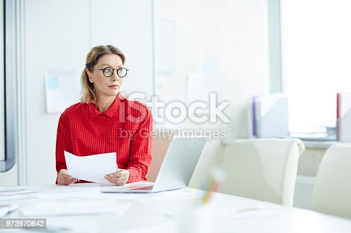 istock Pensive serious woman with papers in office 973970642