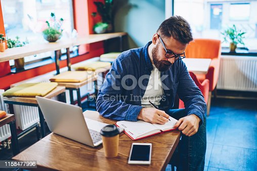1174436608 istock photo Pensive skilled bearded student dressed in denim shirt writing down studying plan in notepad sitting at modern laptop computer in coworking space.Hipster guy noting text information in notebook 1158477996