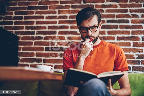 1174436608 istock photo Pensive smart bearded student reading studying task in textbook and thinking on solution.Thoughtful intelligent young man in eyeglasses learning information from book preparing for upcoming exams 1168818721