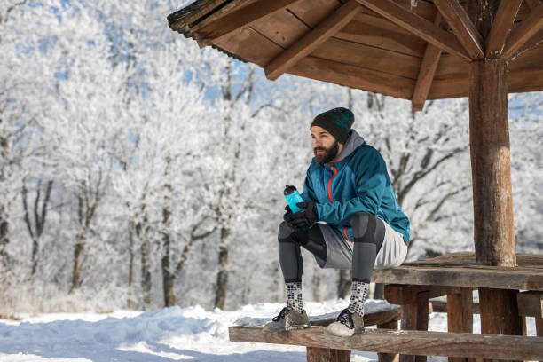 Pensive sportsman having a water break during winter day in nature. Young athletic man resting on a water break in winter day at the park. groyne stock pictures, royalty-free photos & images
