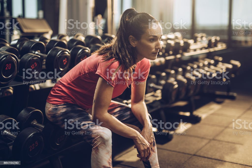 Pensive sportswoman taking a break in a health club. royalty-free stock photo
