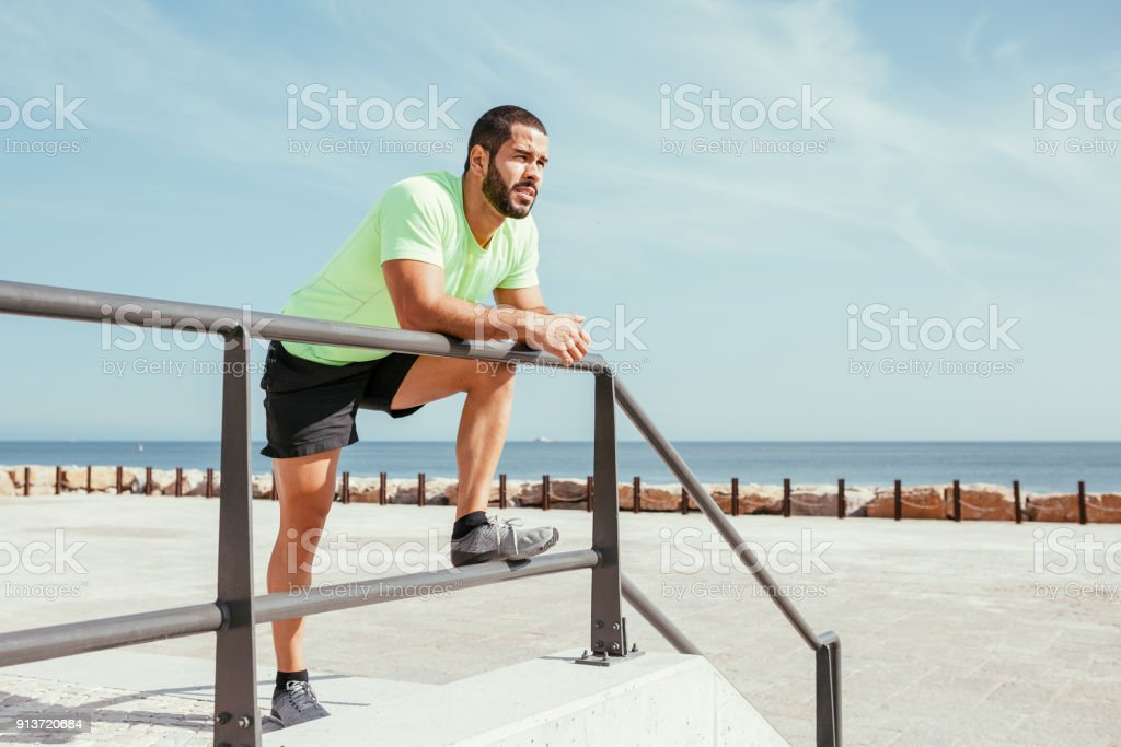 pensive sporty man relaxing and leaning on railing stock photo