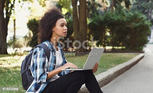 1009493672istockphoto Pensive student sitting on stairs using laptop 913003988