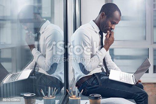 istock Pensive stylish businessman is making important task 891010944