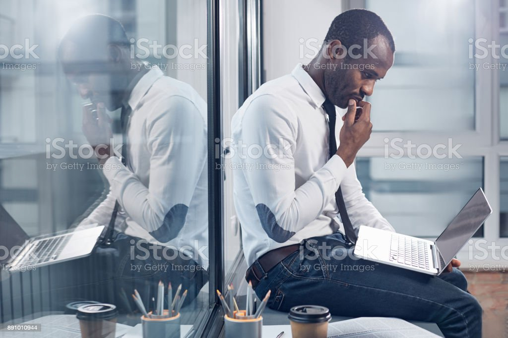 Pensive stylish businessman is making important task stock photo
