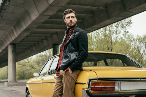 pensive stylish man in leather jacket standing near vintage car and looking away - appoggiarsi foto e immagini stock