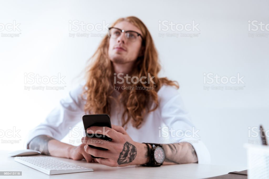 pensive stylish tattooed businessman with curly hair holding smartphone and looking up royalty-free stock photo