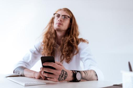 곱슬 머리를 들고 스마트폰 찾고 잠겨있는 세련 된 문신된 실업가 경영자에 대한 스톡 사진 및 기타 이미지