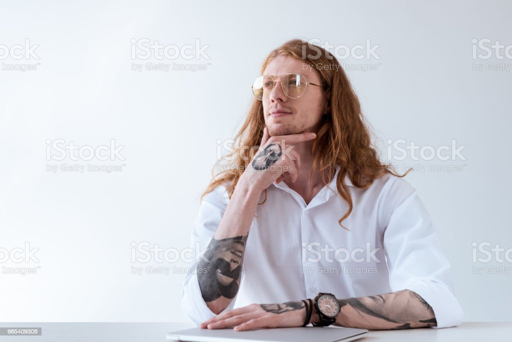 pensive stylish tattooed businessman with curly hair looking away isolated on white zbiór zdjęć royalty-free