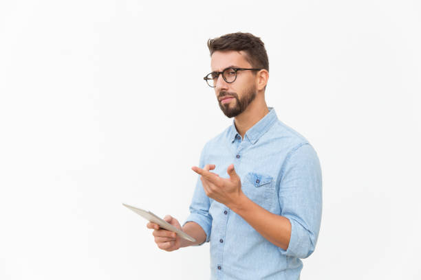 Pensive tablet user looking at camera and pointing finger away stock photo