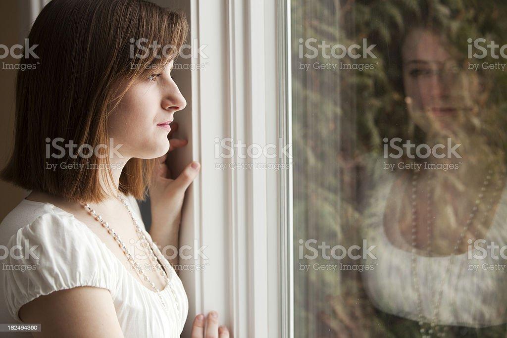 Pensive Teen Girl Looks Away Near Window Reflection royalty-free stock photo