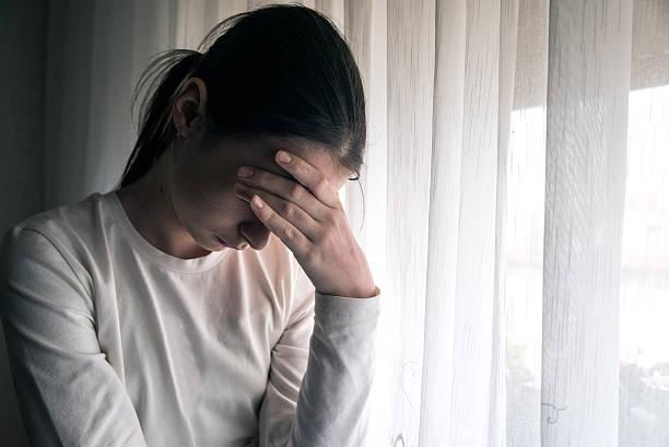 pensive teenager holding head with her hand - frisuren 2016 frauen stock-fotos und bilder
