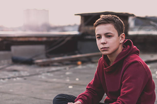 Pensive teenager sitting on the roof of the house stock photo