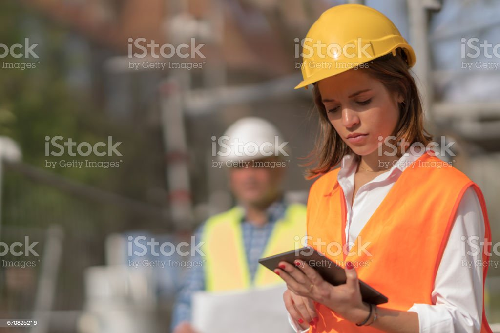 Pensive, thoughtful young civil engineer working with her touchless tablet on construction site stock photo