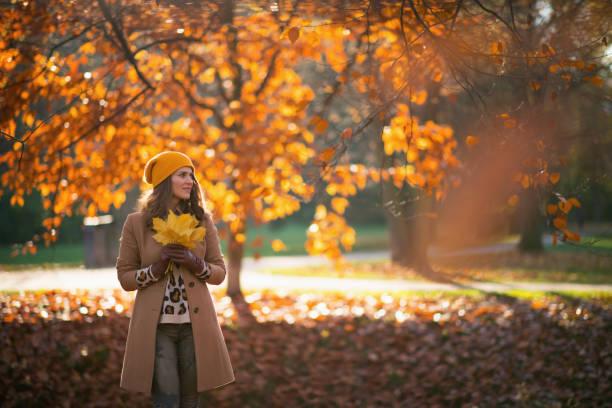 pensive trendy woman in beige coat and orange hat stock photo