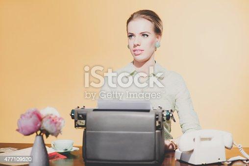 istock Pensive vintage 1950 blonde secretary woman sitting behind desk 477109520