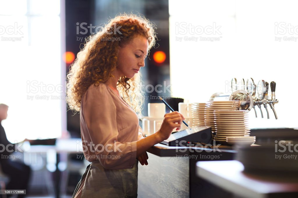 Serveuse songeuse ajout commande au restaurant POS - Photo