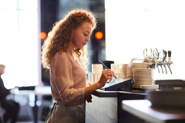 Pensive waitress adding order in restaurant POS stock photo