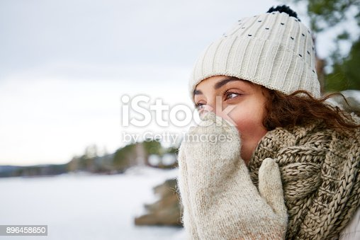 Introspective beautiful young woman warming up nose with mittens while walking in forest