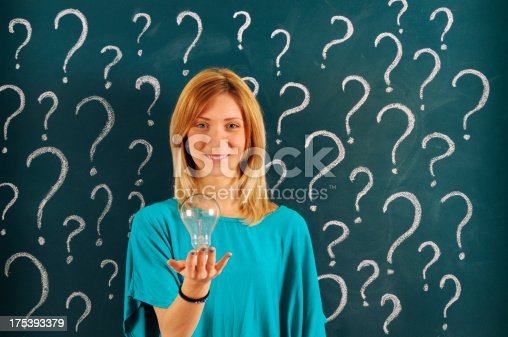Pensive Woman Holding Light Bulb in front of Blackboard