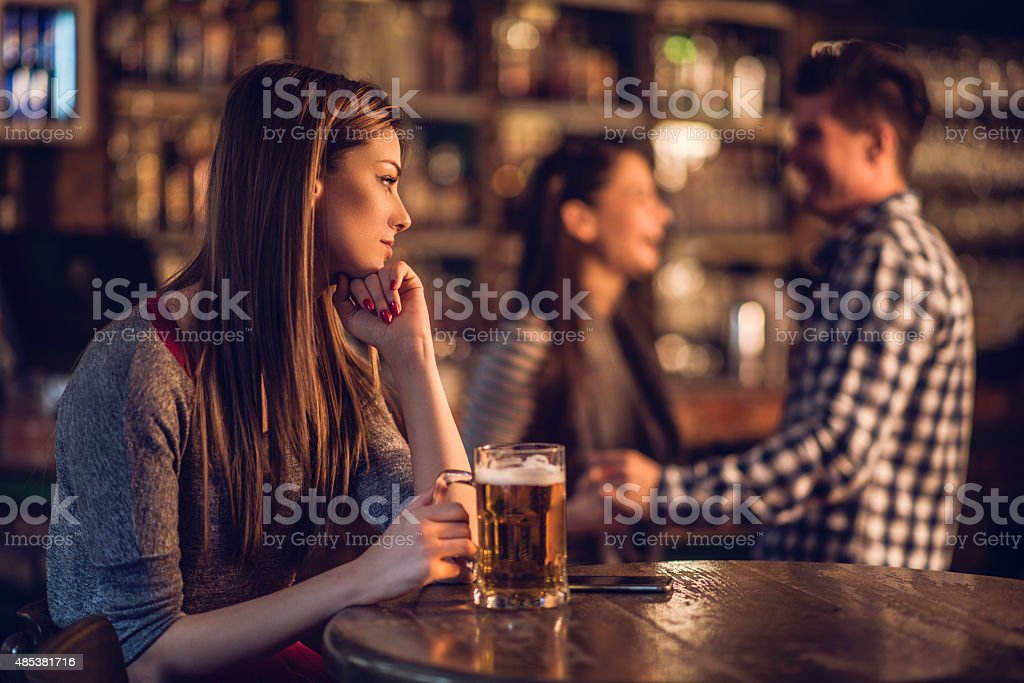 Pensive woman in bar looking at happy couple in background. stock photo