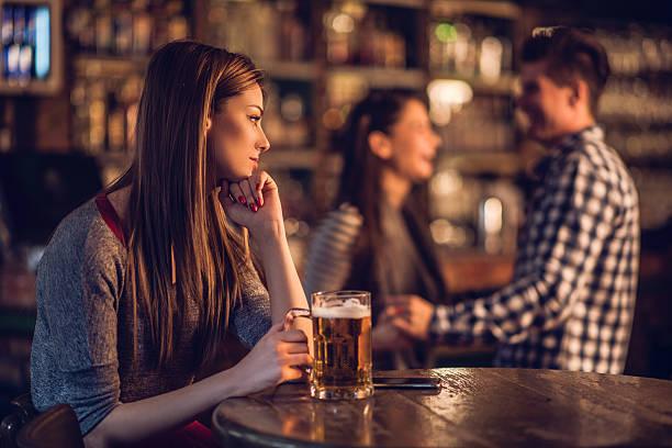 哀愁女性バーでお求めのカップルのバックグラウンド。 - 羨望 ストックフォトと画像
