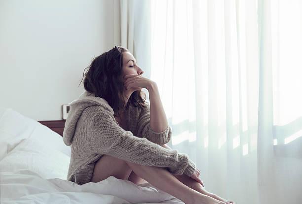 哀愁女性のベッド - 負の感情 ストックフォトと画像