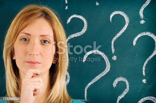 695936656 istock photo Pensive Woman in front of Question Marks Sketched on Blackboard 175386204