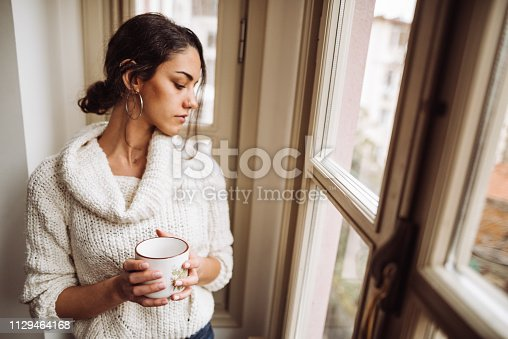 917874758 istock photo pensive woman in front of the window 1129464168