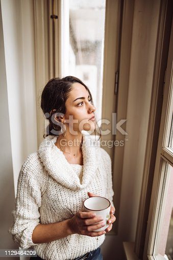 917874758 istock photo pensive woman in front of the window 1129464209