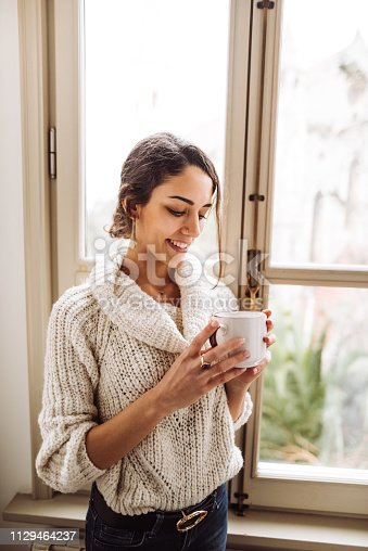 917874758 istock photo pensive woman in front of the window 1129464237
