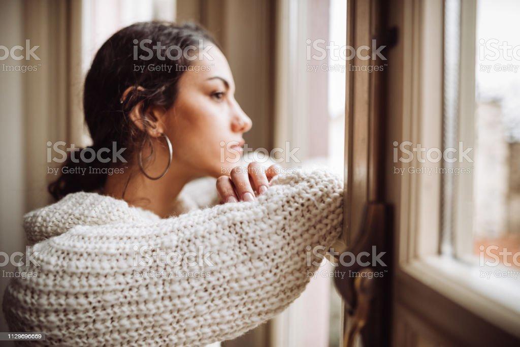 ウィンドウの前面に物思いにふける女 - 1人のロイヤリティフリーストックフォト