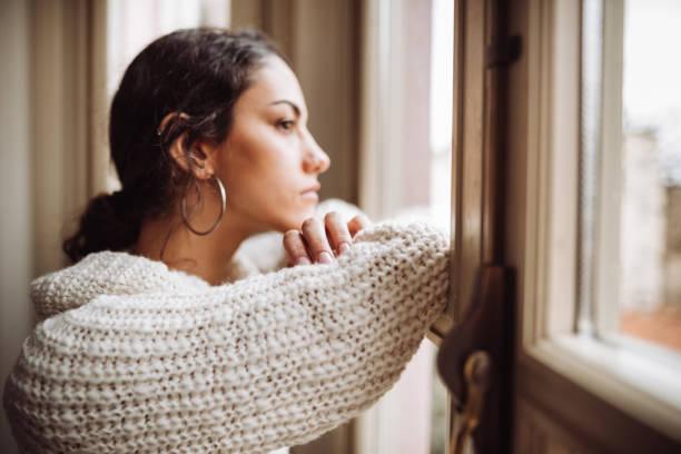 nachdenkliche frau vor dem fenster - depression stock-fotos und bilder